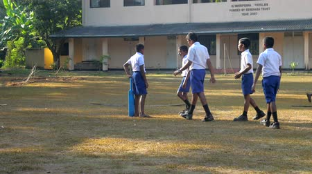 schoolyard : ColomboSRI LANKA - APRIL 05 2019: Schoolboys gather on playground against school building to play cricket slow motion. Concept sport and competition on April 05 in Colombo