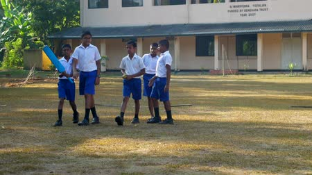összejövetel : ColomboSRI LANKA - APRIL 05 2019: Schoolboys walk along green playground to play cricket with smiles slow motion. Concept school sport and competition on April 05 in Colombo Stock mozgókép