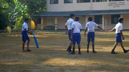 schoolyard : ColomboSRI LANKA - APRIL 05 2019: Sinhalese boys in uniforms prepare for cricket game on playground against school building slow motion. Concept sport and competition on April 05 in Colombo