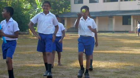 schoolyard : ColomboSRI LANKA - APRIL 05 2019: Boys in uniforms walk along playground preparing for cricket game slow motion. Concept sport and competition on April 05 in Colombo