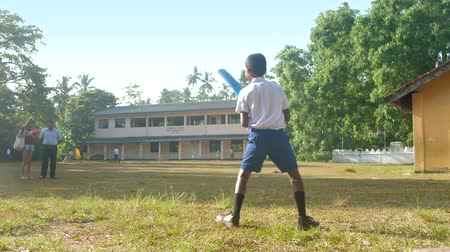cricket : ColomboSRI LANKA - APRIL 05 2019: Sinhalese schoolboy holds blue cricket bat and runs on school playground slow motion. Concept sport and competition on April 05 in Colombo
