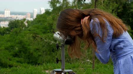 outlook : young woman in blue dressing looks into observation telescope standing at distance from city. Concept travel