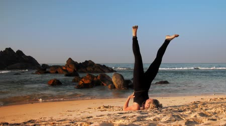 продвинутый : slim woman in black tracksuit practices advanced shoulder stand pose in morning on sandy ocean beach extreme slow motion. Concept fitness yoga practice health
