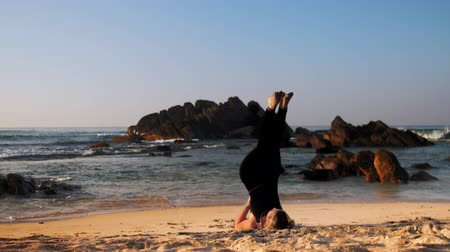 meditál : lady in black tracksuit meditates in yoga supported shoulder stand on ocean beach in morning against waves extreme slow motion. Concept meditation spiritual practice