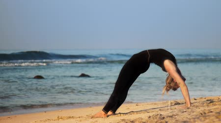 meditál : blond girl in black tracksuit meditates in yoga pose wheel on ocean beach against azure waves extreme slow motion. Concept meditation spiritual practice yoga Stock mozgókép