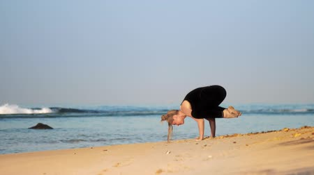 meditál : fit blond woman meditates in yoga pose crow on sandy ocean coast against rolling azure waves slow motion. Concept meditation yoga sport healthy lifestyle