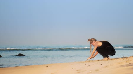 hatha : blonde girl with space buns in black tracksuit practices yoga on sand ocean beach against azure waves and blue sky slow motion. Concept healthy lifestyle sport yoga