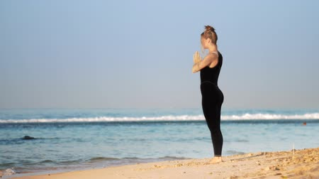 meditál : beautiful lady in sportswear meditates at sunrise on sunlit sandy beach against azure ocean extreme slow motion. Concept meditation spiritual practice Stock mozgókép