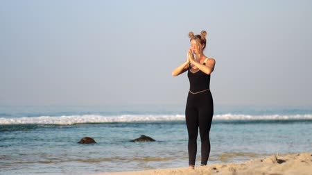 hatha : fair haired female with space buns changes yoga poses in warm summer morning on sandy beach against azure ocean waves slow motion. Concept spiritual practices yoga