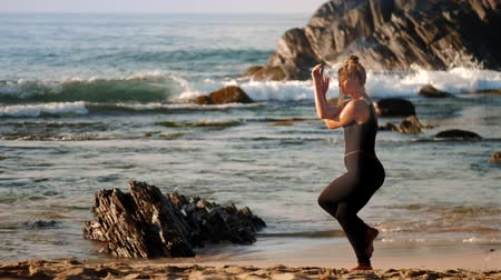 sas : sporty female in black tracksuit practices yoga pose eagle on ocean beach against rising sun azure ocean and big rocks slow motion. Concept healthy lifestyle yoga