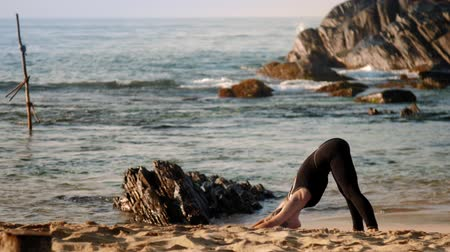 cobra : blonde girl changes yoga pose downward-facing dog to cobra pose on sunlit morning beach against azure ocean and big brown rocks slow motion. Concept healthy lifestyle yoga