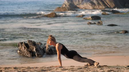 裸足 : woman with space buns does yoga pose cobra on sandy beach in morning against azure ocean with brown rocks extreme slow motion. Concept yoga sport