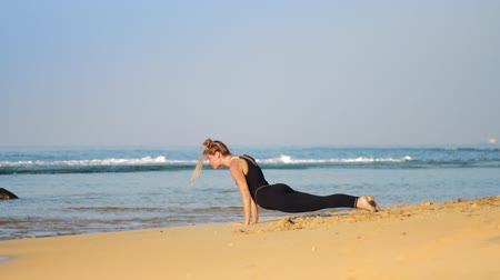 cobra : beautiful blonde girl in black tracksuit practices yoga pose cobra on sunlit sandy beach against rolling waves and blue sky slow motion. Concept yoga healthy lifestyle