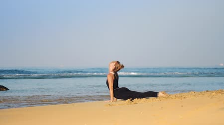 cobra : slim blond girl in black tracksuit meditates in yoga pose cobra in morning on warm sand beach against azure ocean and clear blue sky slow motion. Concept yoga fitness