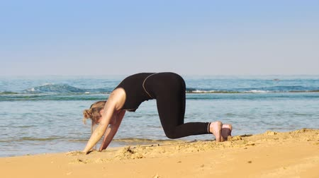 plavé vlasy : fair haired girl in black tracksuit changes yoga poses on warm sandy ocean beach against rolling waves slow motion. Concept yoga spiritual practices