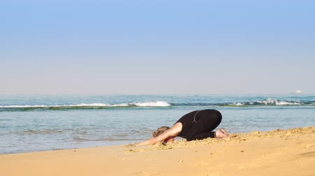 meditál : beautiful woman with space buns meditates in yoga pose child on warm sunlit beach against azure ocean and boundless blue sky slow motion. Concept yoga relaxation, nature