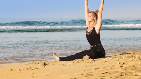 esneme : gorgeous blond lady does stretching on golden sunlit beach in warm morning against amazing ocean and clear blue sky slow motion. Concept relaxation stretching Stok Video