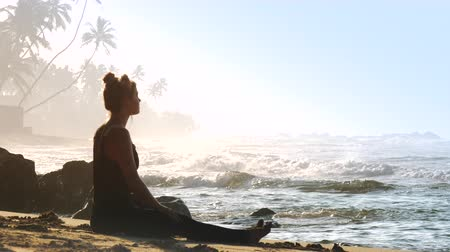 meditál : young woman with space buns meditates on wild beach against incredible breathtaking landscape of ocean with rolling waves and palm trees slow motion. Concept sport relaxation, nature, travel
