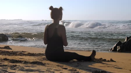 meditál : young lady in black tracksuit meditates on sunlit sandy ocean beach against dark rocks and deep azure ocean slow motion. Concept yoga meditation relax, travel Stock mozgókép