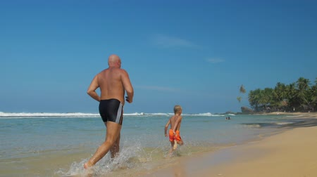 vagabundo : happy family of little boy and strong daddy runs in clear shallow water on ocean beach under blue sky slow motion. Concept fatherhood vacation nature Vídeos