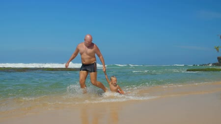 тянущий : happy father plays with adorable son pulling kid by hand in ocean water against blue sky slow motion. Concept fatherhood vacation
