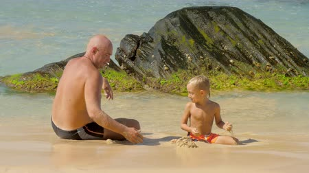 przedszkolak : positive daddy and cute small son throw wet sand playing in water on tropical ocean beach slow motion. Concept fatherhood vacation