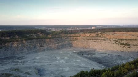 minério : grey large gravel quarry with special mining technic against town with green trees on foreground aerial view. Concept mining old technology