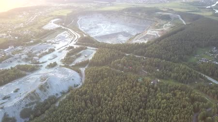 szektor : tremendous barrow and gravel quarry surround grey road at green forest lit by summer setting sun light aerial view. Concept environmental change