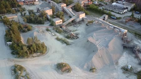moloz : crushed stone production equipment at grey rubble barrows surrounded by dense forests in summer upper view. Concept environmental change old technology Stok Video
