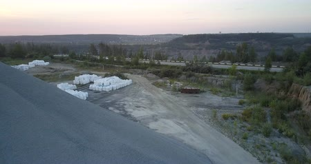 nakládané : loaded white bags clusters against grey road with rubble barrow on foreground in summer evening dusk aerial view. Concept environmental change