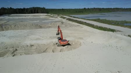 agresif : aerial motion above red modern excavator at huge sand pit near calm lakes in summer. Concept environmental change