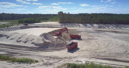 minério : TYUMENRUSSIA - JULY 22 2018: Powerful digger loads sand into tipper workbody in developed pit near green forest bird eye view. Concept ecosystem disturbance on July 22 in Tyumen