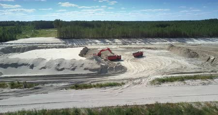 változatosság : TYUMENRUSSIA - JULY 22 2018: Camera rises above large sand pit with excavator loading ore into dump truck workbody in summer. Concept aggressive development of nature on July 22 in Tyumen Stock mozgókép