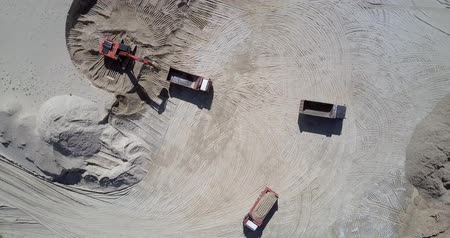 minério : powerful red excavator fills empty tipper workbody with ore at huge sand quarry in summer aerial view. Concept environmental change