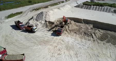agresif : TYUMENRUSSIA - JULY 22 2018: Aerial motion to empty dump truck driving to excavator at huge sand hill in open pit on sunny day aerial view. Concept aggressive development of nature on July 22 in Tyumen