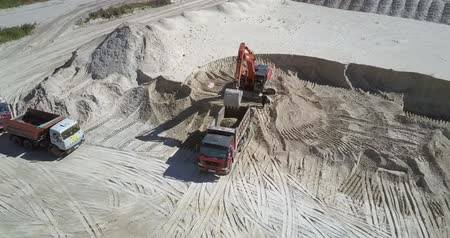 minério : TYUMENRUSSIA - JULY 22 2018: Red powerful digger loads ore into empty workbody of tipper at large sand quarry on summer day upper view. Concept environmental change on July 22 in Tyumen Vídeos