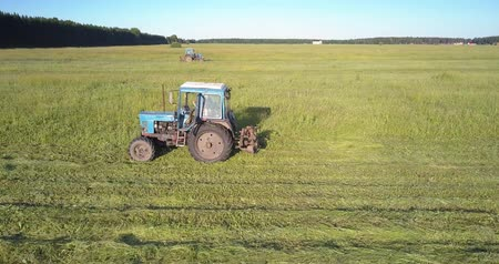 széna : aerial view experienced driver drives hay baler cutting off grass against peaceful rural nature Stock mozgókép