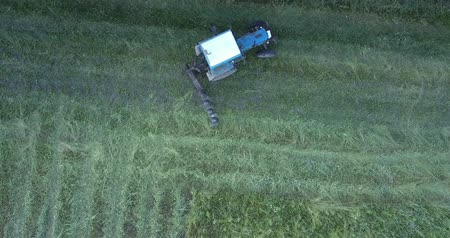 turning off : panoramic view mechanism with rotating blade moves along field turning and cutting off grass in agricultural area