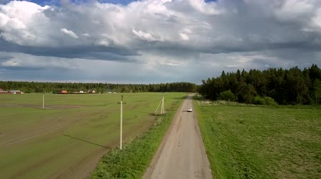 лесное хозяйство : white car drives along destructed road between green dense forest and field with power lines under cloudy sky aerial view. Concept road destruction