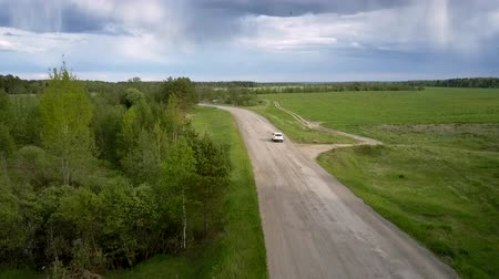 лесное хозяйство : modern automobile drives carefully along gray road with pits under cloudy sky on summer day upper view. Concept abandoned road and rural hinterland Стоковые видеозаписи