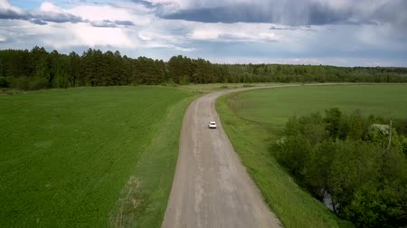 old pit : white sport utility vehicle drives around pits on old asphalt road near green meadow against forest upper view. Concept abandoned road and countryside Stock Footage