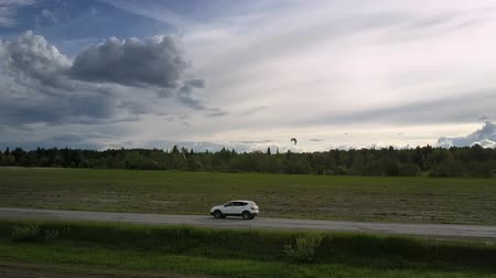 hasznosság : modern automobile drives along gray road between fields against forest under pictorial sky upper view. Concept road destruction and speed