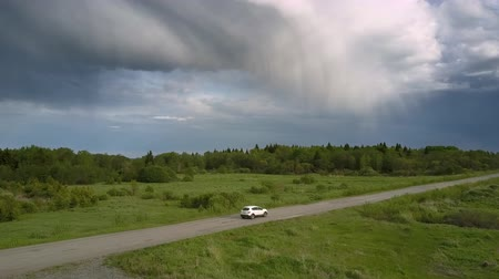 crossover : modern automobile drives along bad ruined road against green endless dense forest in summer aerial view. Concept abandoned road and countryside Stock Footage