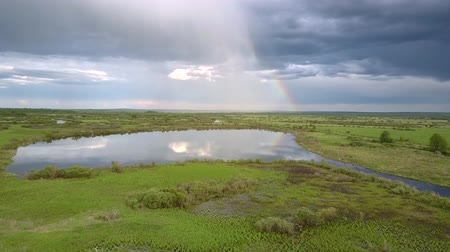 лесное хозяйство : tranquil lake reflects clouds near green grass and trees with rainbow on horizon in summer aerial view. Concept countryside and environmental change Стоковые видеозаписи