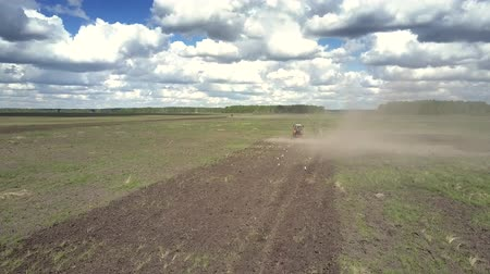 furrow : interesting picture flycam follows tractor operating in dust cloud birds peck grain on fresh furrow on boundless field