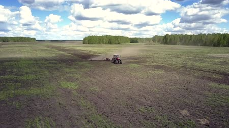 agronomia : fantastic upper view red tractor plows dark soil with wide harrow in dust cloud against sky and white clouds