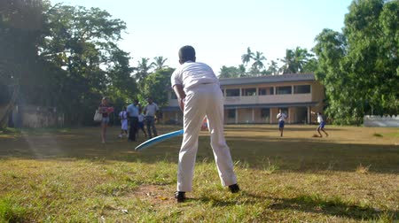 bat : ColomboSRI LANKA - APRIL 05 2019: Schoolboy bats flying ball on autumn cricket game against school building slow motion backside view. Concept sport and competition on April 05 in Colombo Stock Footage