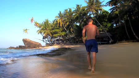 bum : barefoot sportsman runs along pictorial ocean coastline under blue summer sky slow motion backside view. Concept fitness and healthy lifestyle