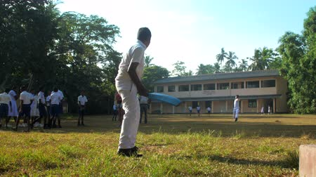 schoolyard : ColomboSRI LANKA - APRIL 05 2019: Sinhalese boy in white school uniform bats cricket ball on sunny autumn day slow motion backside view. Concept sport and healthy lifestyle on April 05 in Colombo