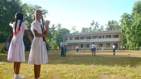 schoolyard : ColomboSRI LANKA - APRIL 05 2019: Sinhalese girls in school uniform look at boys playing cricket on sunny autumn day slow motion. Concept sport and competition on April 05 in Colombo Stock Footage